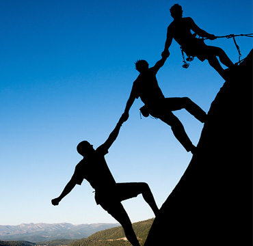 Team of climbers roped together climbing a hill